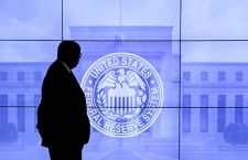 A security guard walks in front of an image of the Federal Reserve in Washington, DC, U.S., March 16, 2016. REUTERS/Kevin Lamarque/File Photo  - RTSV8Y6