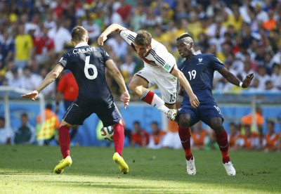 Germany's Thomas Mueller is tackled by France's Paul Pogba  (R) near France's Yohan Cabaye during their 2014 World Cup quarter-finals at the Maracana stadium in Rio de Janeiro July 4, 2014. REUTERS/Pilar Olivares (BRAZIL  - Tags: SOCCER SPORT WORLD CUP)