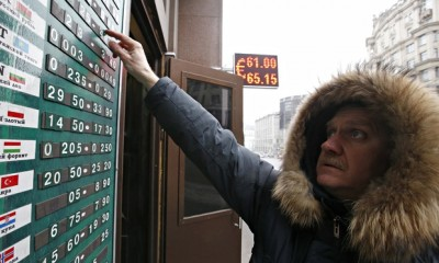 An employee changes figures on a board showing currency exchange rates in Moscow