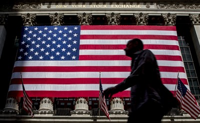 A morning commuter passes by the U.S. flag hung on the facade of New York Stock Exchange July 6, 2015. REUTERS/Brendan McDermid   - RTX1J9GU